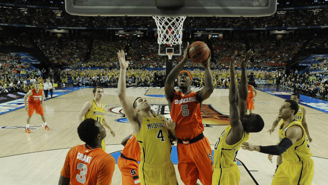 Syracuse's C.J. Fair (5) heads to the hoop against Michigan's Mitch McGary (4) during the second half of the NCAA Final Four tournament college basketball semifinal game Saturday, April 6, 2013, in Atlanta. (AP Photo/NCAA Photos, Chris Steppig, Pool)