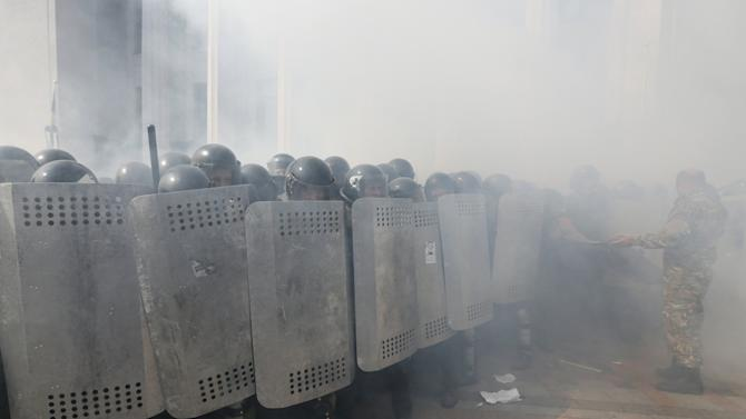 Ukrainian police officers take cover behind shields during clashes with demonstrators, who are against a constitutional amendment on decentralization, outside the parliament building in Kiev
