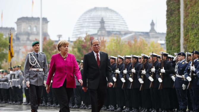 German Chancellor Merkel and Philippine President Aquino inspect honour guard before talks at Chancellery in Berlin