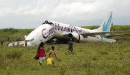 The broken fuselage of a Caribbean Airlines' Boeing 737-800 is seen after it crashed at the end of the runway at Cheddi Jagan International Airport in Timehri, Guyana, Saturday July 30, 2011. The Caribbean Airlines flight 523 from New York touched down on the rainy runway, slid through a chain-link fence and broke apart just short of a ravine but there were no immediate reports of death among the 163 people aboard, despite several dozen of injuries. (AP Photo/Jules Gibson)
