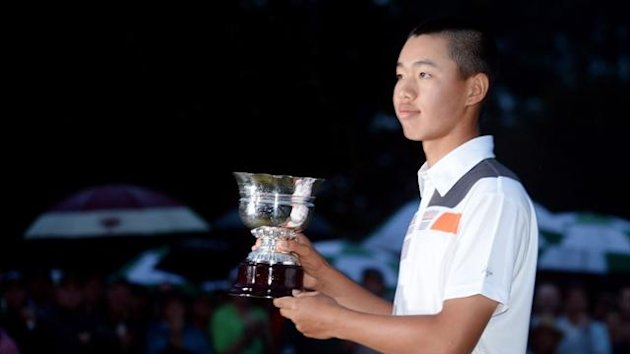 Tianlang Guan of China poses after winning low amateur honours after the final round of the 2013 Masters Tournament at Augusta National Golf Club (AFP)