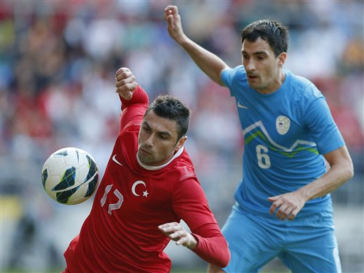 Turkey's Burak Yilmaz, left, and Slovenia's Branko Ilic challenge for the ball during the friendly soccer match between Turkey and Slovenia in Bielefeld, Germany, Friday, May 31, 2013