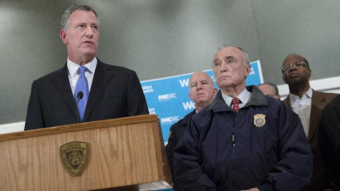 ADDS BOTH OFFICERS KILLED - New York City Mayor Bill de Blasio, left, speaks alongside NYPD Commissioner Bill Bratton, right, stands beside during a news conference at Woodhull Medical Center, Saturday, Dec. 20, 2014, in New York.  An armed man walked up to two New York Police Department officers sitting inside a patrol car and opened fire Saturday afternoon, killing both officers before running into a nearby subway station and committing suicide, police said. (AP Photo/John Minchillo)