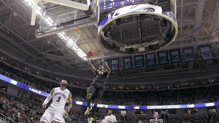 Oregon guard Damyean Dotson (21) drives to the basket against Saint Louis guard Kwamain Mitchell (3) during the first half of a third-round game in the NCAA college basketball tournament Saturday, March 23, 2013, in San Jose, Calif. (AP Photo/Tony Avelar)