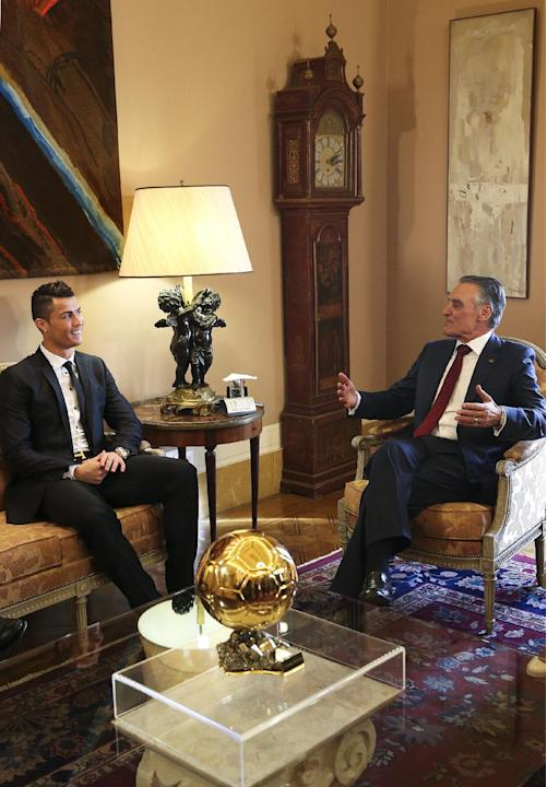 Portugal's soccer team captain Cristiano Ronaldo shows Portuguese President Anibal Cavaco Silva, right, his world's best player Golden Ball award during a meeting Monday, Jan. 20 2014, at the
