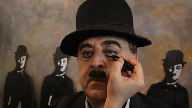 A member of Charlie Circle, a Charlie Chaplin fan-club gets made up before the annual parade to celebrate the birthday of Charlie Chaplin, in Adipur, Gujarat state, India, Tuesday, April 16, 2013. Canes in hand and bowler hats firmly in place, dozens of Charlie Chaplin impersonators tramped through the streets of this small port town in western India on Tuesday to celebrate the birthday of the legendary comic actor and filmmaker. (AP Photo/Ajit Solanki)