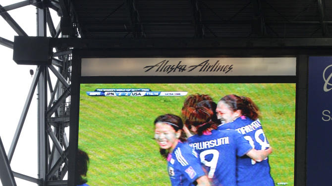Highlights from the FIFA Women's World Cup soccer match between USA and Japan are shown on a scoreboard screen during a baseball game between the Texas Rangers and the Seattle Mariners, Sunday, July 17, 2011, in Seattle. (AP Photo/Ted S. Warren)