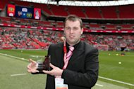 A member of staff at Oxford United FC accepts the award for League 2 Programme of the year on the pitch