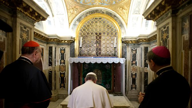 In this picture made available by the Vatican newspaper L'Osservatore Romano, Pope Francis, flanked by Cardinal Angelo Comastri, left, and Bishop Vittorio Lanzani, right, kneels in prayer in front of what is believed to be the burial site of St. Peter's in the necropolis where pagans and early Christians were buried under St. Peter's Basilica at the Vatican, Monday, April 1, 2013, during what was called the first-ever visit by a pope to the necropolis. The basilica was built over the location where early Christians would gather in secret, at a time of persecution in ancient Rome, to pray at an unmarked tomb believed to be that of Peter, the apostle Jesus chose to lead his church. (AP Photo/L'Osservatore Romano)