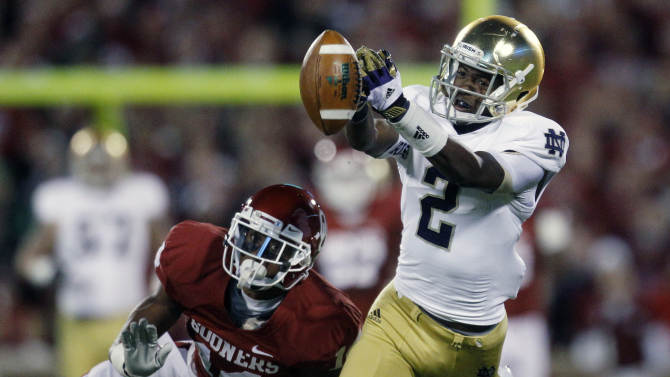 Notre Dame wide receiver Chris Brown (2) can't hold onto a pass in front of Oklahoma defensive back Aaron Colvin (14) in the first quarter of an NCAA college football game in Norman, Okla., Saturday, Oct. 27, 2012. (AP Photo/Sue Ogrocki)