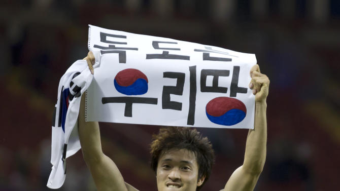 "FILE - This is a  Friday, Aug. 10, 2012 file photo of South Korea's Park Jong-woo as he holds up a banner reading ""Dokdo is our Territory,"" referring to the largely uninhabited islets, midway between South Korea and Japan, after his team won their bronze medal men's soccer match against Japan, at the 2012 London Summer Olympics, at the Millennium Stadium in Cardiff, Wales.  Rark Jong-woo who raised political tensions with Japan by displaying a political sign at the London Olympics after the countries' bronze-medal match was banned for two World Cup qualifying matches on Monday Dec. 3, 2012. FIFA said Park Jong-woo was guilty of unsporting behavior which ""cannot be tolerated,"" and formally warned the Korea Football Association. (AP Photo/Jon Super, File)"
