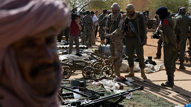 Malian soldiers look on as weapons, munitions, and other paraphernalia seized from radical Islamist rebels are displayed at the French army base in Gao, Mali, Sunday, Feb. 24, 2013. The Chadian army said Saturday that its troops had killed 65 Islamic extremist rebels and destroyed five vehicles in the Adrar des Ifoghas mountains of northeastern Mali. According to the statement, 13 Chadian soldiers were also killed and six were wounded in the fighting Friday.(AP Photo)