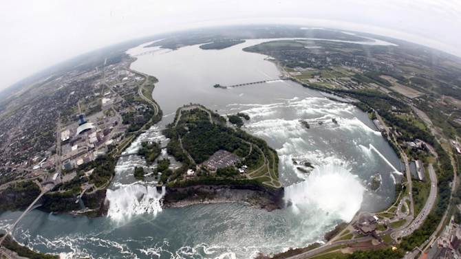 FILE - In this June 3, 2009 photo, Ruedi Hafen, not shown, president and chief pilot of Niagara Helicopters Ltd., flies over Niagara Falls in Niagara Falls, Ontario. In recent years, for economic reasons, Niagara Falls has thrown open its doors to casino gambling, gay weddings and a tightrope walk that, until laws were relaxed, would have meant arrest. It even briefly considered taking in toxic wastewater from hydraulic fracturing. On the drawing board now is a plan to entice young people to move in by paying down their student loans. (AP Photo/David Duprey, File)