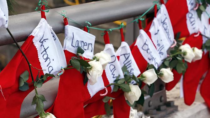 FILE - In this Wednesday, Dec. 19, 2012 file photo, Christmas stockings with the names of shooting victims hang from railing near a makeshift memorial near the town Christmas tree in the Sandy Hook village of Newtown, Conn. In the wake of the shooting, the grieving town is trying to find meaning in Christmas. (AP Photo/Julio Cortez, File)