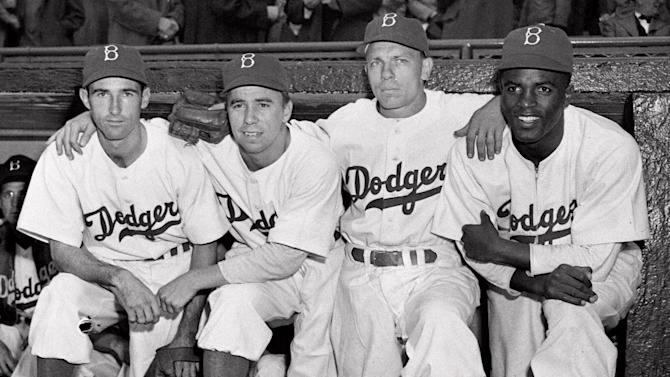 "FILE - In this April 15, 1947 file photo,  from left, Brooklyn Dodgers baseball players John Jorgensen, Pee Wee Reese, Ed Stanky and Jackie Robinson pose at Ebbets Field in New York. Kansas City's Negro Leagues Baseball Museum is hosting an advance screening of an upcoming movie about Robinson, who broke major league baseball's color barrier. Thomas Butch of the financial firm Waddell and Reed announced Wednesday, March 20, 2013 that actors Harrison Ford and Andre Holland will be among those appearing at an April 11 screening of ""42.""   (AP Photo, File)"