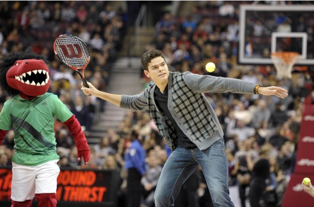 Canadian tennis player Raonic hits tennis balls to fans during the Raptors and Hawks NBA basketball game in Toronto