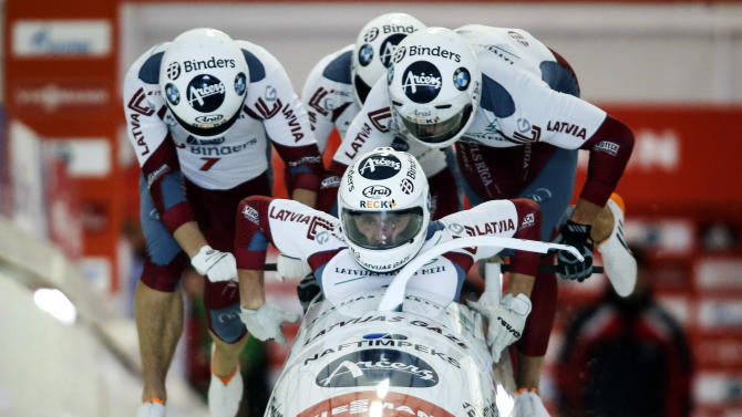 Latvia's Oskars Melbardis, Daumants Dreiskens, Arvis Vilkaste, and Janis Strenga, compete in the men's World Cup 4-man bobsled event in Calgary, Saturday, Dec. 20, 2014. (AP Photo/The Canadian Press, Jeff McIntosh)