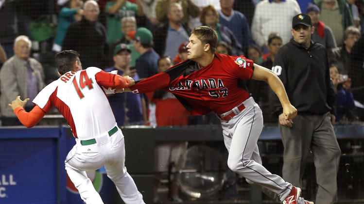 Canada's Jay Johnson, right, and Mexico's Eduardo Arredondo, left, fight during the ninth inning of a World Baseball Classic game on Saturday, March 9, 2013, in Phoenix. (AP Photo/Matt York)