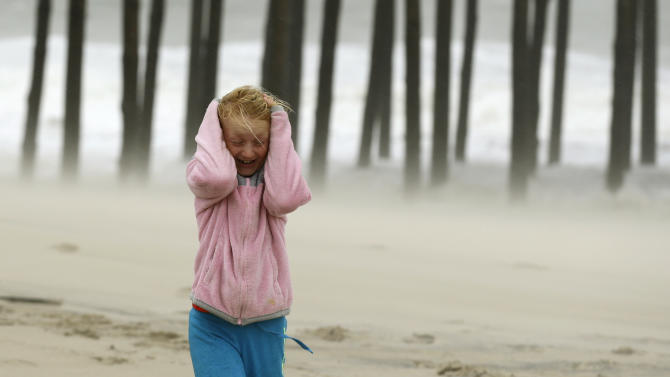 Molly White, 9, from Frankford, Del., covers her head as she is pelted by blowing sand on the beach, as Hurricane Sandy bears down on the East Coast, Sunday, Oct. 28, 2012, in Ocean City, Md. (AP Photo/Alex Brandon)