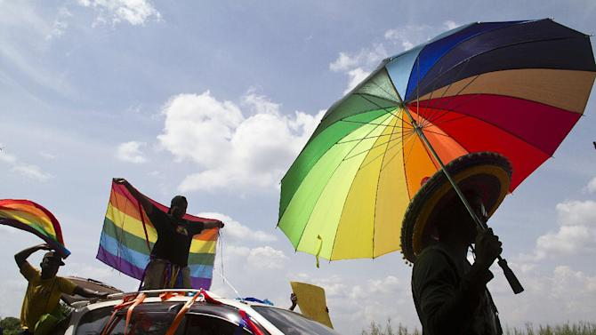 Revellers in Entebbe wave flags during the the first gay pride rally since the overturning of Uganda's anti-homosexuality laws, on August 9, 2014
