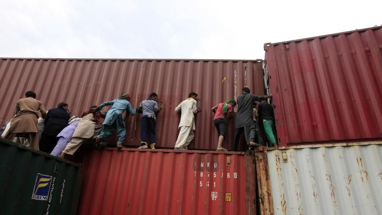 Anti-government protesters climb a container barricade, attempting to push it over, during the Revolution March in Islamabad