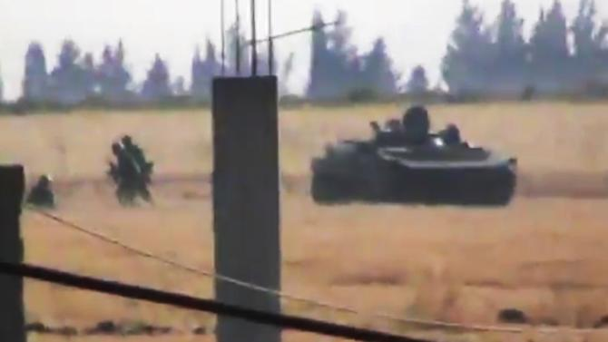 This image made from amateur video released by the Shaam News Network and accessed Monday, June 18, 2012, purports to show a Syrian military tank in Daraa, Syria. Regime forces have been waging a fierce offensive through towns and villages nationwide, trying to root out rebels by shelling urban areas with tanks and attacking from helicopters. Rebels also have attacked Syrian forces, mostly trying to burn tanks. (AP Photo/Shaam News Network via AP video) TV OUT, THE ASSOCIATED PRESS CANNOT INDEPENDENTLY VERIFY THE CONTENT, DATE, LOCATION OR AUTHENTICITY OF THIS MATERIAL