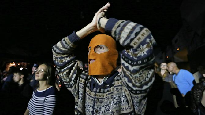 A masked spectator  reacts during the concert organized to support  jailed Pussy Riot musicians in  St.Petersburg, Russia, Sunday, Sept. 9, 2012. A Moscow judge has sentenced each of three members of the provocative punk band Pussy Riot to two years in prison on hooliganism charges following a trial that has drawn international outrage as an emblem of Russia's intolerance to dissent. (AP Photo/Dmitry Lovetsky)