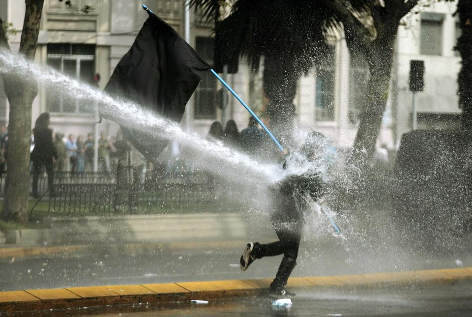 A protester gets sprayed by a water canon during a May Day march in Santiago, Chile, Tuesday, May 1, 2012. Clashes with security forces and riots marred the rally to mark International Labor Day. (AP Photo/Luis Hidalgo)