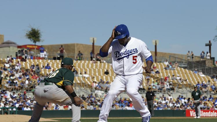 Los Angeles Dodgers' Juan Uribe (5) gets back to first on a pickoff play in a spring exhibition baseball game Monday, March 10, 2014, in Glendale, Ariz. (AP Photo/Mark Duncan)