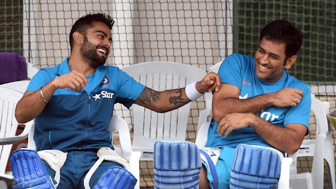 India's Virat Kohli (L) and Mahendra Singh Dhoni share a joke during a training session in Melbourne, on March 18, 2015
