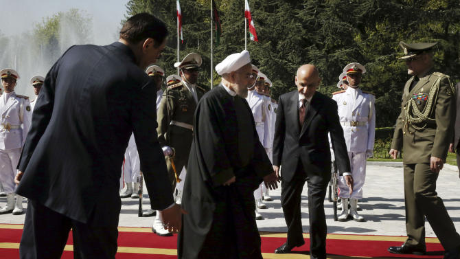 Afghan President Ashraf Ghani, second right, is welcomed by his Iranian counterpart Hassan Rouhani, second left, during his official welcoming ceremony at the Saadabad palace in Tehran, Iran, Sunday, April 19, 2015. (AP Photo/Vahid Salemi)