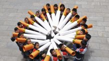"Students pose for pictures with ""big cigarette models"" during campaign ahead of World No Tobacco Day, at primary school in Handan"