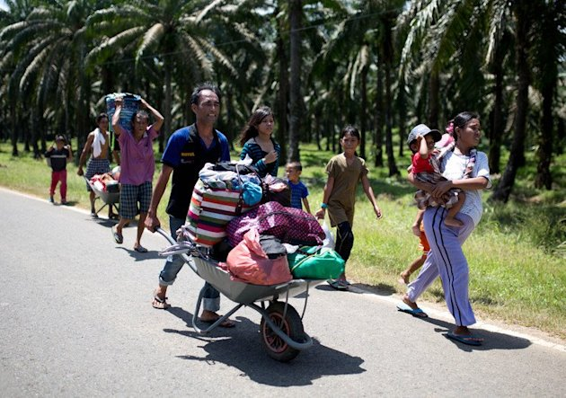 Residents of Tanjung Labian flee their village, in the area where Filipino gunmen are locked in a stand-off with Malaysian security forces, in Sabah state, on March 10, 2013. Malaysian police said on Sunday two officers were injured in shootouts with the gunmen as they try to end their month-long incursion that has already left 61 people dead