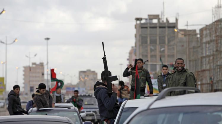 Libyan gunmen celebrate on the early morning of the second anniversary of the revolution that ousted Moammar Gadhafi, in Benghazi, Libya, Sunday, Feb. 17, 2013.  (AP Photo/Mohammad Hannon)