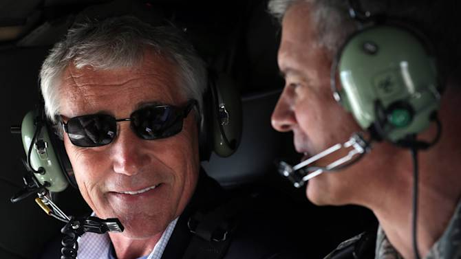 """U.S. Secretary of Defense Chuck Hagel, left, talks to Commander of U.S. Force Japan Lt. Gen. Salvatore """"Sam"""" Angelella during a helicopter ride Saturday, April 5, 2014 from Yokota Air Force Base in Fussa, to Tokyo in Japan. Hagel is on an Asian trip, the fourth since he took office, to Japan, China and Mongolia. (AP Photo/Alex Pool, Pool)"""