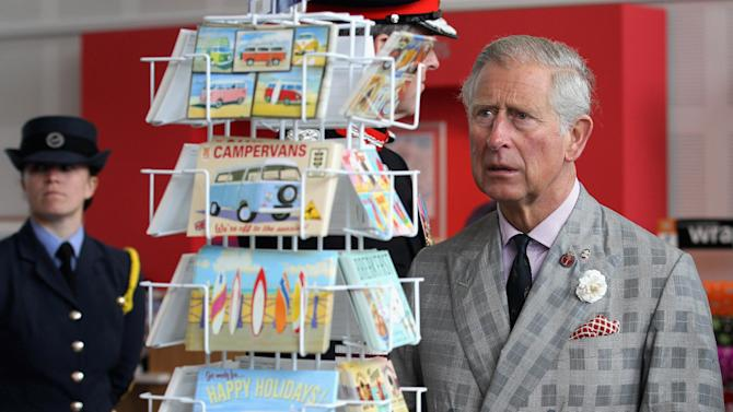 FILE - In this July 2, 2012 file photo, Britain's Prince Charles, right, looks at postcards on sale during a visit to the Heartlands Community Regeneration Project in Truro, southwest England. Attorney General Dominic Grieve on Tuesday, Oct. 16, 2012 overruled a court ruling last month that the public had a right to see what sort of advice Britain's Prince Charles was offering to the British government. (AP Photo/Chris Jackson, Pool-File)