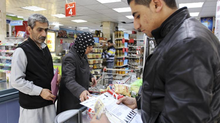 Syrian refugees pay for grocery with vouchers they received from the WFP at a supermarket in Amman