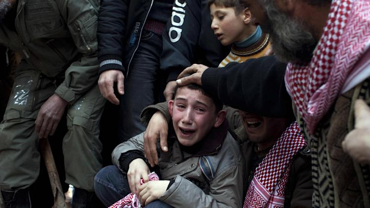 FOR USE AS DESIRED, YEAR END PHOTOS - FILE - In this March 8, 2012 file photo, Ahmed, center, mourns his father Abdulaziz Abu Ahmed Khrer, who was killed by a Syrian Army sniper, during his funeral in Idlib, north Syria. (AP Photo/Rodrigo Abd, File)