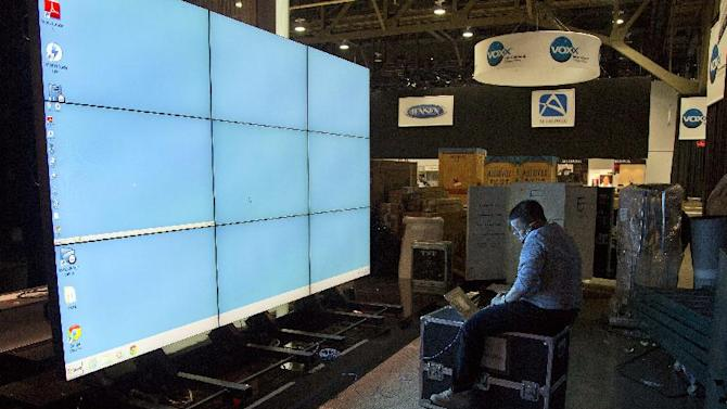 Sharp Electronics employee Michael Nenortas programs a flat screen display at the company's booth for the International Consumer Electronics Show, Sunday, Jan. 6, 2013, in Las Vegas. The show, which drew more than 3,100 exhibitors in 2012 and is open only to industry affiliates, begins Tuesday and runs through Friday. (AP Photo/Julie Jacobson)