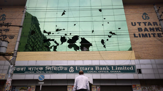 A man stands in front of his office building damaged by Bangladeshi protesters during a protest in Savar near Dhaka, Bangladesh, Monday, May 6, 2013. At least 15 people died in clashes Monday in Bangladesh between police and Islamic hardliners demanding that Bangladesh implement an anti-blasphemy law, police said. (AP Photo/Ismail Ferdous)