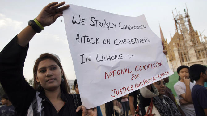 Pakistani Christian women hold a placard during a demonstration to condemn the torching homes of their community by mob in Lahore, Saturday, March 09, 2013 in Karachi, Pakistan. A mob of hundreds of people in the eastern Pakistani city of Lahore attacked a Christian neighborhood Saturday and set fire to homes after hearing accusations that a Christian man had committed blasphemy against Islam's prophet, said a police officer. (AP Photo/Fareed Khan)
