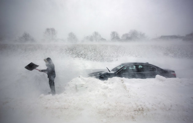 A woman digs out her car after it was blocked in by drifting snow during a blizzard, Saturday, Feb. 9, 2013, in Portland, Maine. The storm dumped more than 30 inches of snow as of Saturday afternoon,