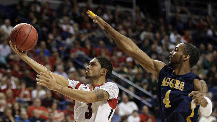 Louisville guard Peyton Siva (3) drives to the basket as North Carolina A&T forward DaMetrius Upchurch (4) defends during the second half of a second-round game in the NCAA college basketball tournament, Thursday, March 21, 2013, in Lexington, Ky. (AP Photo/John Bazemore)