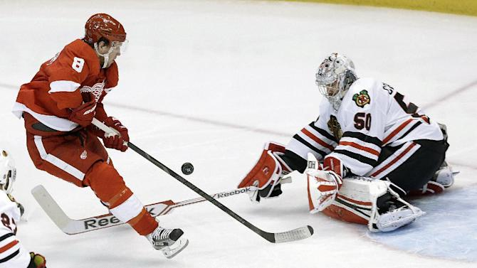 Chicago Blackhawks goalie Corey Crawford (50) stops a shot by Detroit Red Wings left wing Justin Abdelkader (8) during the second period of an NHL hockey Stanley Cup playoffs Western Conference semifinal game in Detroit, Monday, May 20, 2013. (AP Photo/Paul Sancya)