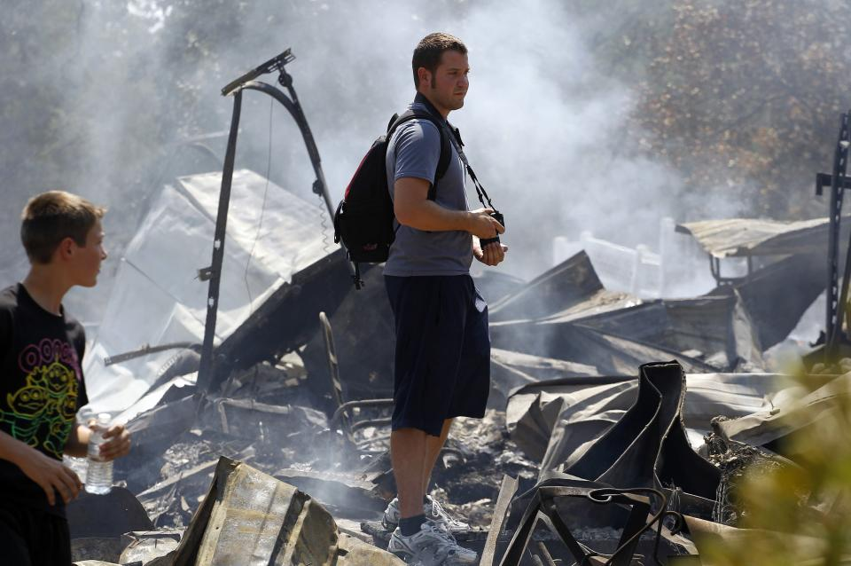 Brothers Ben, left, and Nathan Clements survey their fire-destroyed home, Tuesday, Sept. 6, 2011, in Bastrop, Texas. The Clements lost their home to fires Monday. (AP Photo/Eric Gay)