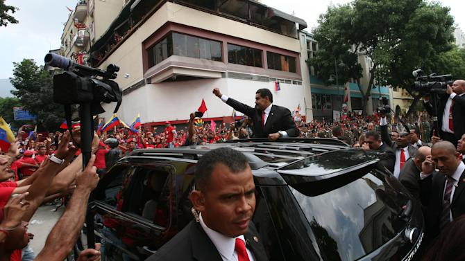 President-elect Nicolas Maduro waves to supporters as he arrives to the Venezuelan Parliament building for his swearing-in ceremony in Caracas, Venezuela, Friday, April 19, 2013. The opposition boycotted the swearing-in, hoping that the ruling party's last-minute decision to allow an audit of nearly half the vote could change the result in a the bitterly disputed presidential election. (AP Photo/Gil Montano)