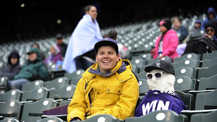 Andrew Tollerud from Lakewood, Colo., sits in the stands with a snowman during the sixth inning in the first game of a doubleheader against the New York Mets Tuesday, April 16, 2013, in Denver. (AP Photo/Jack Dempsey)