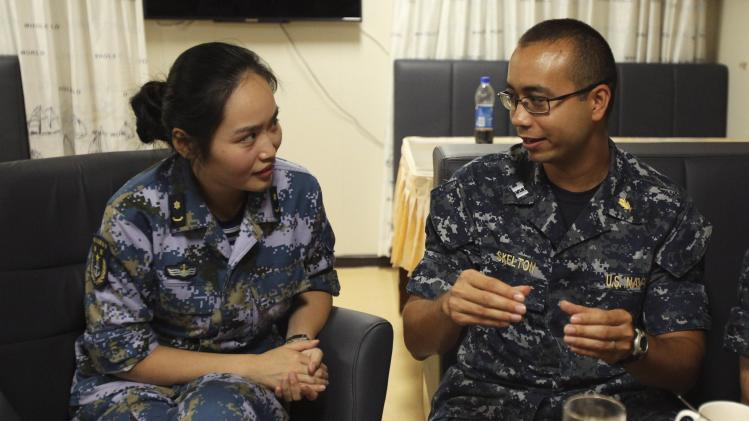 U.S. Navy medic Lieutenant Skelton talks to Naval Lieutenant Xie of China's PLA while aboard the PLA ship Peace Ark during the RIMPAC in Honolulu