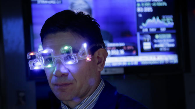 A trader wears glasses celebrating the new year while working on the floor at the New York Stock Exchange in New York, Tuesday, Dec. 31, 2013. (AP Photo/Seth Wenig)