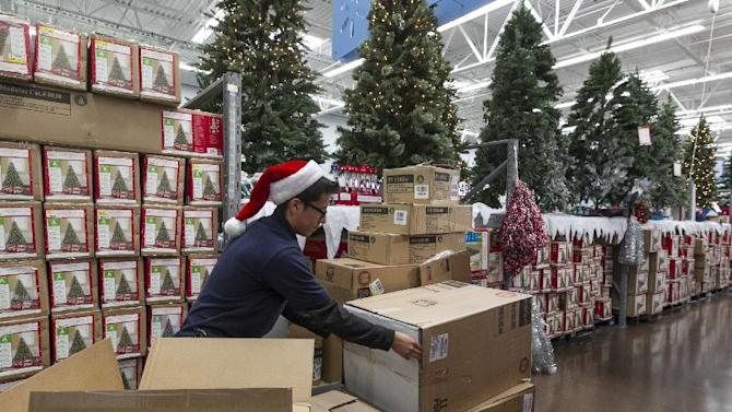 Walmart associate Angel Campos stocks Christmas decorations ahead of the Pre-Black Friday event at the Walmart Supercenter store in Rosemead, Calif., Wednesday, Nov. 21, 2012. (AP Photo/Damian Dovarganes)